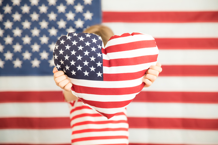 Child holding heart printed American flag. 4th of July, Independence day holiday. Patriotism and democracy concept 写真素材