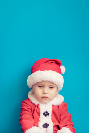 Portrait of sad child. Funny kid wearing Santa Claus costume. Christmas holiday concept