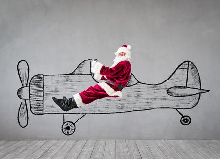 L'homme senior du Père Noël voyage par avion. Concept de vacances de Noël Noël