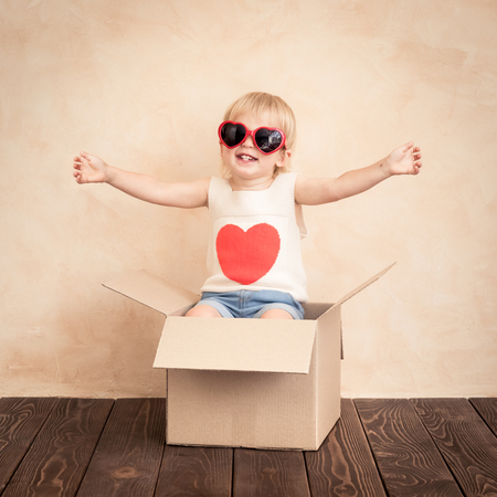 Happy child with red heart. Funny kid playing at home. Valentines day concept