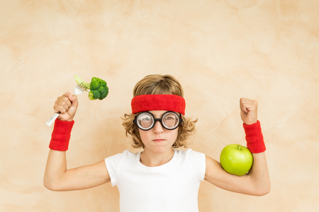 Sportrsman nerd child eating superfood. Geek kid holding broccoli and apple. Healthy eating and lifestyle concept. Green vegetarian food Zdjęcie Seryjne