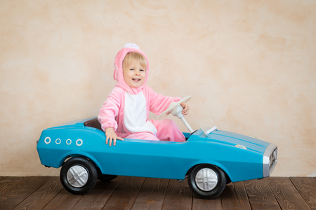 Funny kid wearing Easter bunny. Child riding toy car at home. Spring holidays concept Stock Photo - 115344625