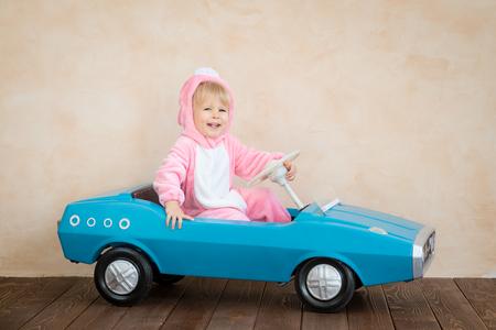 Niño gracioso con conejito de Pascua. Niño montando coche de juguete en casa. Concepto de vacaciones de primavera