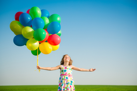 Happy child playing with bright multicolor balloons outdoor. Kid having fun in green spring field against blue sky background. Healthy and active lifestyle concept Stock Photo