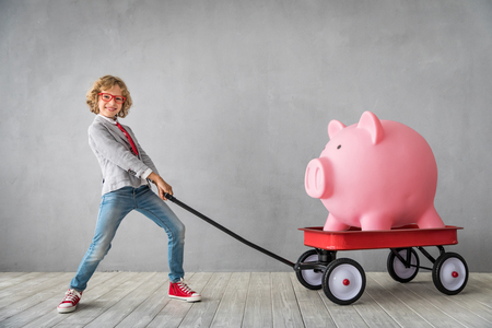 Child with giant piggy bank. Success, finance and investment concept Banco de Imagens