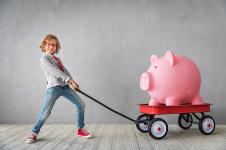 Kind mit riesigem Sparschwein. Erfolgs-, Finanz- und Anlagekonzept Standard-Bild