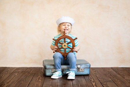 Happy child pretend to be sailor. Funny kid playing at home. Summer vacation and travel concept