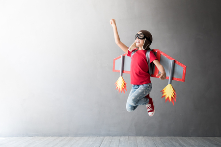 Happy child playing with toy jetpack. Kid pilot having fun at home. Success, innovation and leader concept Stockfoto - 115343789