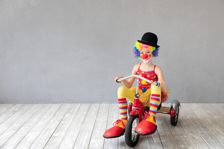 Funny kid clown riding tricycle. Happy child playing at home. 1 April Fools day concept