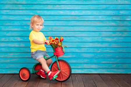 Lustiges Kinderfahrrad. Glückliches Kind, das Spaß zu Hause hat. Frühlingskonzept für den Familienurlaub. Muttertag