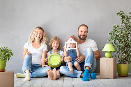Familia feliz con dos niños jugando en casa nueva. Padre, madre e hijos divirtiéndose juntos. Día de la mudanza y concepto de bienes raíces. Foto de archivo
