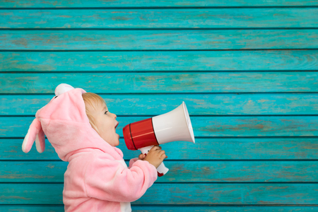Funny kid wearing Easter bunny. Child speaking by megaphone. Spring holidays concept Stockfoto