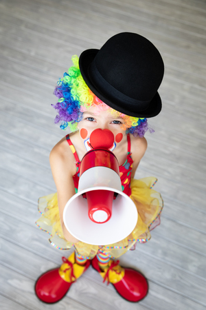 Funny kid clown. Happy child playing at home. 1 April Fool's day concept 免版税图像 - 115561236