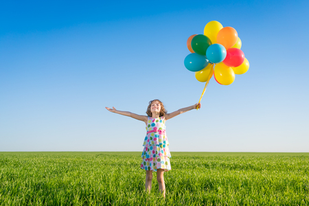 Happy child playing with bright multicolor balloons outdoor. Kid having fun in green spring field against blue sky background. Healthy and active lifestyle concept Stockfoto