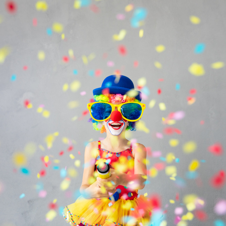 Funny kid clown with party poppers. Happy child playing at home. 1 April Fools day concept