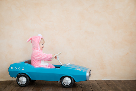 Funny kid wearing Easter bunny. Child riding toy car at home. Spring holidays concept