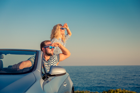 Happy couple travel by car. People having fun in blue cabriolet. Summer vacation concept