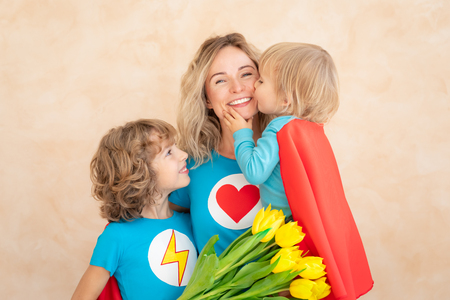Superhero woman and children at home. Mother, daughter and son having fun together. Spring family holiday concept. Mother's day Stock Photo