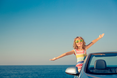 Happy child travel by car. Kid having fun in blue cabriolet. Summer vacation concept