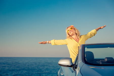 Happy woman travel by car. Person having fun in blue cabriolet. Summer vacation concept