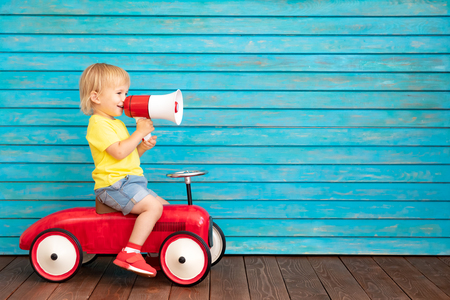Funny child riding bike. Happy kid having fun at home. Spring family holiday concept. Mother's day