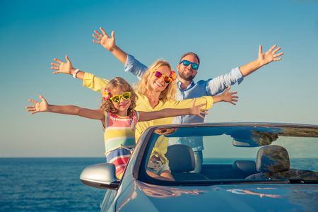 Happy family travel by car. People having fun in blue cabriolet. Summer vacation concept