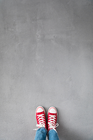 Feet in red sneakers on concrete background