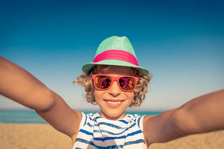 Happy child on summer vacation. Kid having fun on the beach. Active healthy lifestyle Фото со стока