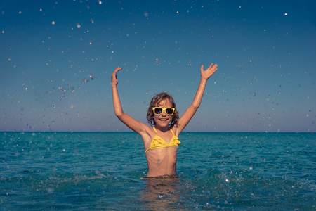 Happy child playing in the sea. Kid having fun on summer vacation. Healthy active lifestyle concept Stock Photo