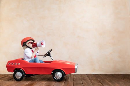 Happy child speaking to megaphone at home. Funny kid driving toy car indoor. Success and win concept Imagens