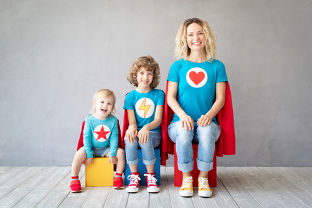 Family of superheroes playing at home. Mother, daughter and son having fun together. Parents with children pretend to be a super heroes Stockfoto