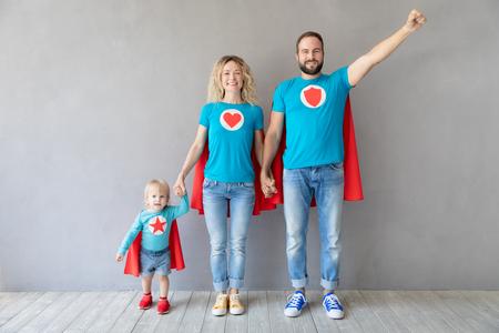 Familia de superhéroes jugando en casa. Padre, madre e hijo se divierten juntos. Los padres con niños se hacen pasar por superhéroes