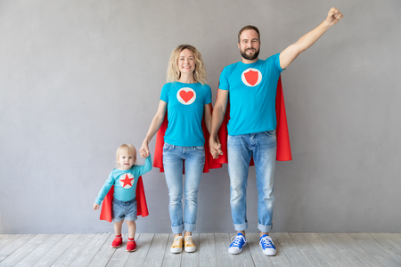 Family of superheroes playing at home. Father, mother and kid having fun together. Parents with child pretend to be a super heroes Foto de archivo - 119343817