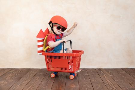 Kind mit Spielzeugpapierrakete. Kind, das zu Hause spielt. Erfolgs-, Vorstellungs- und Innovationstechnologiekonzept Standard-Bild