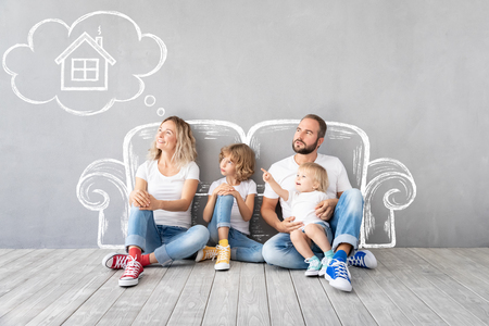 Happy family with two kids playing into new home. Father, mother and children having fun together. Moving house day and real estate concept