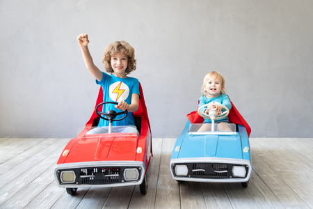 Children superheroes playing at home. Kids having fun together. Winner and success concept