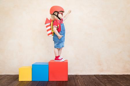 Kind mit Spielzeugpapierrakete. Kind, das zu Hause spielt. Erfolgs-, Vorstellungs- und Innovationstechnologiekonzept