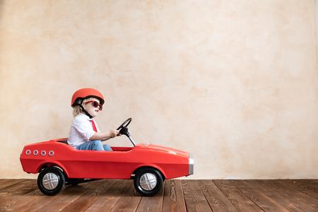 Bambino felice che gioca in casa. Bambino divertente che guida l'automobile del giocattolo al coperto. Successo e concetto di vittoria