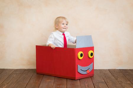 Il bambino felice finge di essere un uomo d'affari. Bambino divertente che gioca a casa. Istruzione, avvio e concetto di idea imprenditoriale Archivio Fotografico