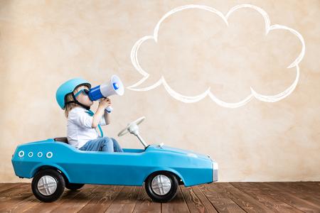 Niño feliz hablando por megáfono en casa. Niño divertido conduciendo un coche de juguete en el interior. Concepto de éxito y victoria