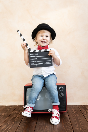 Child playing at home. Kid holding clapper board. Retro cinema concept Stock Photo