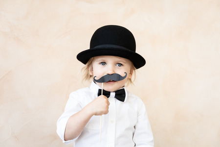 Funny kid with fake paper moustache. Happy child playing in home. Fathers day concept