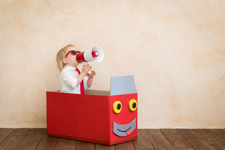 Il bambino felice finge di essere un uomo d'affari. Bambino divertente che parla dal megafono. Istruzione, avvio e concetto di idea imprenditoriale