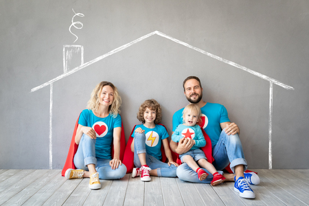 Family of superheroes playing at home. Father, mother, daughter and son having fun together. Parents with children pretend to be a super heroes