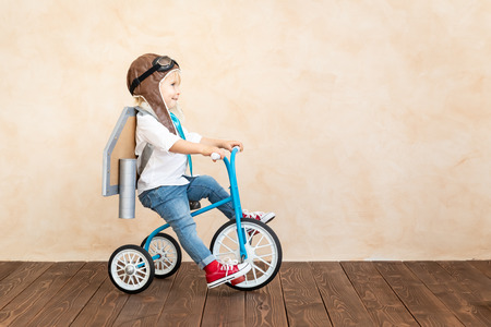 Funny kid with toy jet pack. Happy child playing at home. Success, imagination and innovation technology concept Stock Photo