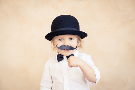 Funny kid with fake paper moustache. Happy child playing in home. Father's day concept