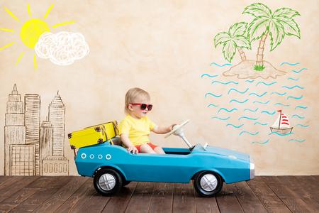 Glückliches Kind, das Spielzeug-Oldtimer reitet. Lustiges Kind, das zu Hause spielt. Sommerurlaub und Reisekonzept