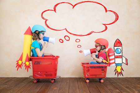 Glückliche Kinder, die zu Hause mit Spielzeugrakete spielen. Lustige Kinder fahren Spielzeugauto drinnen. Erfolgs- und Gewinnkonzept
