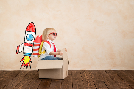 Happy child playing with toy rocket at home. Funny kid driving cardboard box indoor. Success and win concept