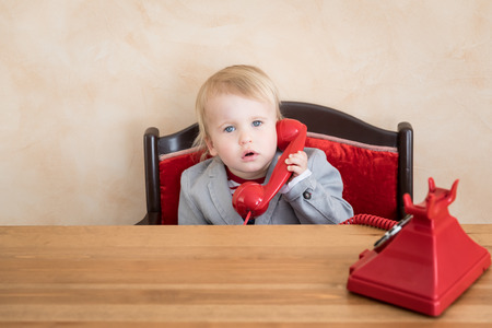 Happy child pretend to be businessmen. Funny kid speaking by phone. Education, start up and business idea concept